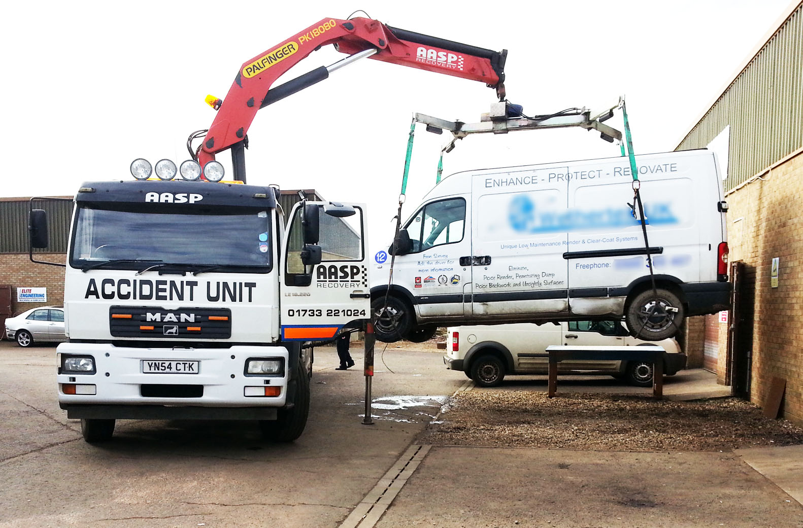 Van being lifted off lorry using crane