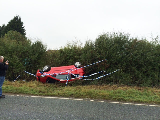 Red car in ditch after accident involving a van